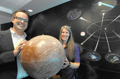 """Johns Hopkins University scientists Joseph Westlake, left, and Elizabeth """"Zibi"""" Turtle are pictured with a globe of Europa, one of Jupiter's moons."""