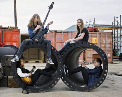 Clockwise from top-left: Bassist Louey Peraza, guitarist Mason Gainer, drummer Aiden Marceron and singer/guitarist Francheska Pastor pose outside their Frederick practice space.