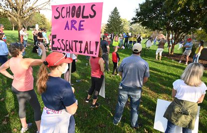 Protesters wanting schools reopened gather around a speaker during a rally outside the Howard County Public School System offices on Thursday, Oct. 22.