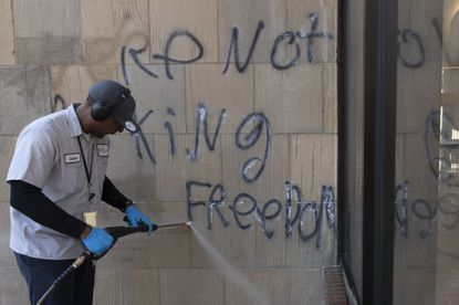 """A worker powers washes to remove spray paint that reads """"We're not asking for freedom"""" on the outside of the Consumer Financial Protection Bureau building in Washington, Monday, June 1, 2020, after a night protests over the death of George Floyd. Floyd died after being restrained by Minneapolis police officers on May 25. (AP Photo/Carolyn Kaster)"""