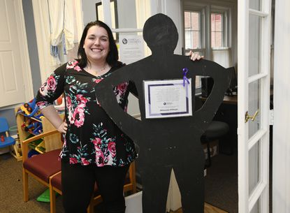 Kelley Rainey, the director of case management for Family and Children's Services, shows one of the office's Lindsay silhouettes, standup cutouts of women that have facts about domestic violence on them, in Westminster on Oct. 16.