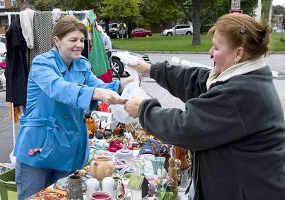 Former Medfield resident Georgia Heffner, right, now of Hereford, still has a booth in front of her former house at the Medfield fall fair and flea market each year. Here, she makes a sale to Hampden resident Donna Hamilton.