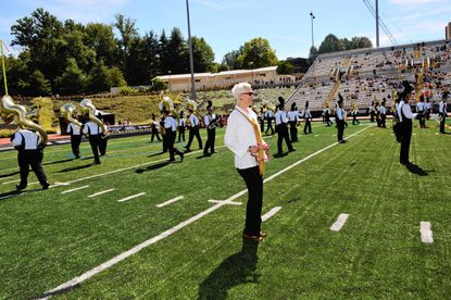 Dr. Maravene Loeschke, president of Towson University, performs with the university's pep band.