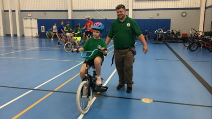 Josh Lemly, a manager at the Churchville Recreation Center, jogs alongside Alaina Alexander as she learns to ride a bicycle with a special rolling pin back wheel during Harford County's Bike Camp Friday.