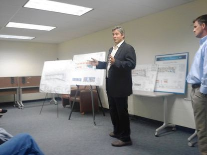 Ned Howe of Enterprise Homes speaks to more than 40 residents who crowded the meeting room at Lansdowne Library on Wednesday evening as Jeff Paxson, of Pax-Edwards, right, looks on. Enterprise and Pax-Edwards are co-developers of a proposed 54-townhouse development on Hollins Ferry Road.