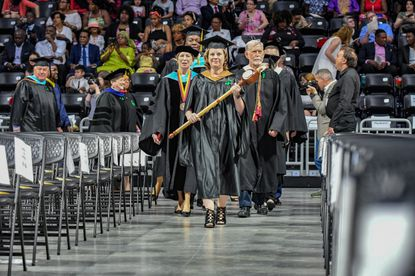 English professor Stacy Korbelak, center, carries the mace followed by Dr. Kathleen Hetherington, President, left, and Kevin J. Doyle, Chair, Board of Trusteess, during the faculty procession at Howard Community College commencement last year. Gov. Larry Hogan has proposed a smaller increase in state aid to community colleges than anticipated next year.