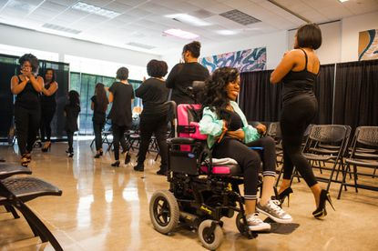 """Keyisha Thomas, center, a model with Sunshine Models on Wheels, practices going down the catwalk with other models before the start of the """"Notice Me Tour"""" at the League for People with Disabilities on Saturday."""