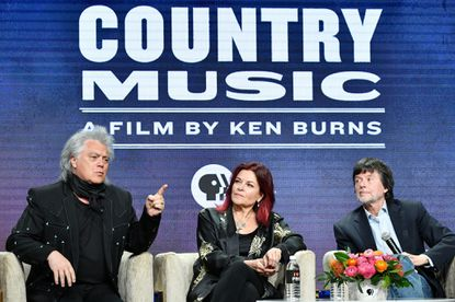 """BEVERLY HILLS, CALIFORNIA - JULY 29: Marty Stuart, Rosanne Cash and Ken Burns of """"Country Music A Film By Ken Burns"""" speak during the PBS segment of the Summer 2019 Television Critics Association Press Tour 2019 at The Beverly Hilton Hotel on July 29, 2019 in Beverly Hills, California."""