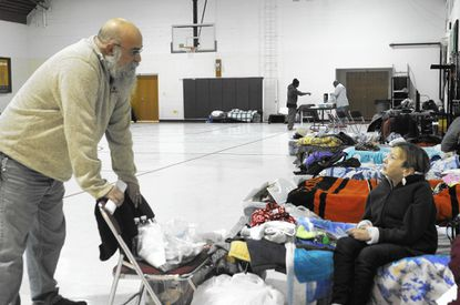Pastor Rick Haynes, head of security for the rotating shelter program run by the Harford County Hope for the Homeless Alliance, talks with guest Carolyn Castello Wednesday at this week's shelter at St. Matthew Lutheran Church in Bel Air.