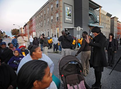 Baltimore Mayor Stephanie Rawlings-Blake, second from right, waves to community members after arriving at the Dawson Family Safe Haven Center for a 10-year commemoration of the family that was killed in a firebombing.