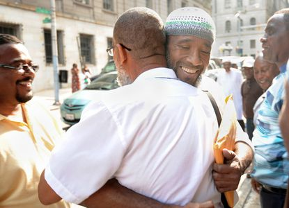 Karriem Saleem El-Amin (facing camera) embraces Alexander Mustafa outside the Baltimore courthouse. El-Amin and five other men convicted in killings were freed as a result of a court ruling.