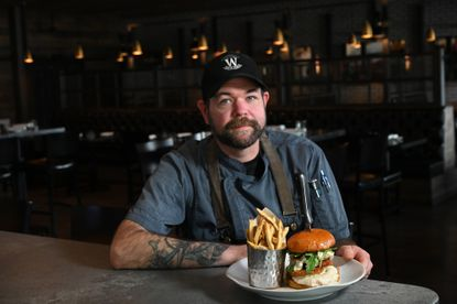 Walker's Tap & Table executive chef Chad Wells with a Crab Daddy Burger and hand-cut fries.