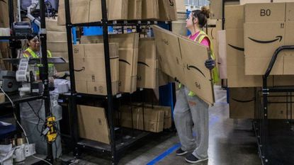 Workers prepare boxes June 8, 2017, at the Amazon warehouse in Romeoville. The company is raising its minimum wage for all U.S. employees to $15 per hour starting in November.