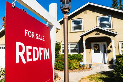 """A Redfin """"for sale"""" sign stands in front of a house Wednesday, Oct. 28, in Seattle. Several fair housing organizations accused Redfin of systematic racial discrimination in a lawsuit Thursday, saying the online real estate broker offers fewer services to homebuyers and sellers in minority communities, a type of """"digital redlining"""" that has depressed home values and exacerbated historic injustice in the housing market."""