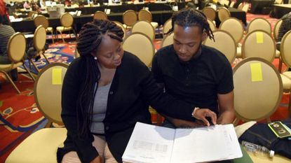 Lynette Wilson and her husband Donnie Brown created a binder to keep track of all the paperwork they need to apply for a mortgage at the Neighborhood Assistance Corporation of America's event Thursday. The five-day event allows people to apply for non-traditional mortgage loans.