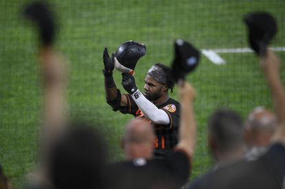 Baltimore Orioles' Cedric Mullins takes a curtain call from the dugout after he hit a three-run home run during the second inning of a baseball game against the Texas Rangers, Friday, Sept. 24, 2021, in Baltimore. (AP Photo/Nick Wass)