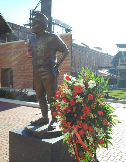 Flowers sit by the statue of Earl Weaver at Camden Yards on Saturday morning.