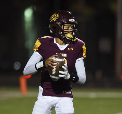 Dunbar quarterback Karon Moore drops back and looks for the open receiver in the first half of Friday night's Class 1A state quarterffnal game against Perryville at Dunbar. User Upload Caption: Dunbar vs Perryville Class 1A football at Dunbar.