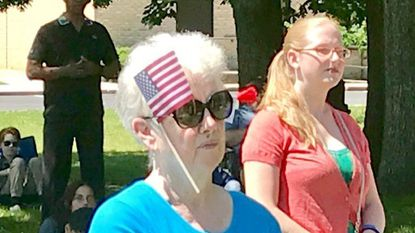 Abingdon resident Linda Domby wears an American flag and a red poppy during the annual Memorial Day celebration in Veterans Memorial Park in Aberdeen Monday morning.