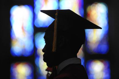 A graduate is silhouetted with stained glass behind him during Calvert Hall's graduation ceremony at Cathedral of Mary Our Queen in Baltimore, on Saturday, June 2.