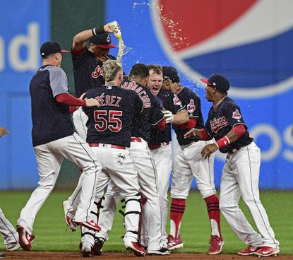 The Indians' Jay Bruce, center, celebrates with teammates after Bruce drove in the winning run with a double off Royals reliever Brandon Maurer during the 10th inning Thursday, Sept. 14, 2017, in Cleveland. The Indians won 3-2.