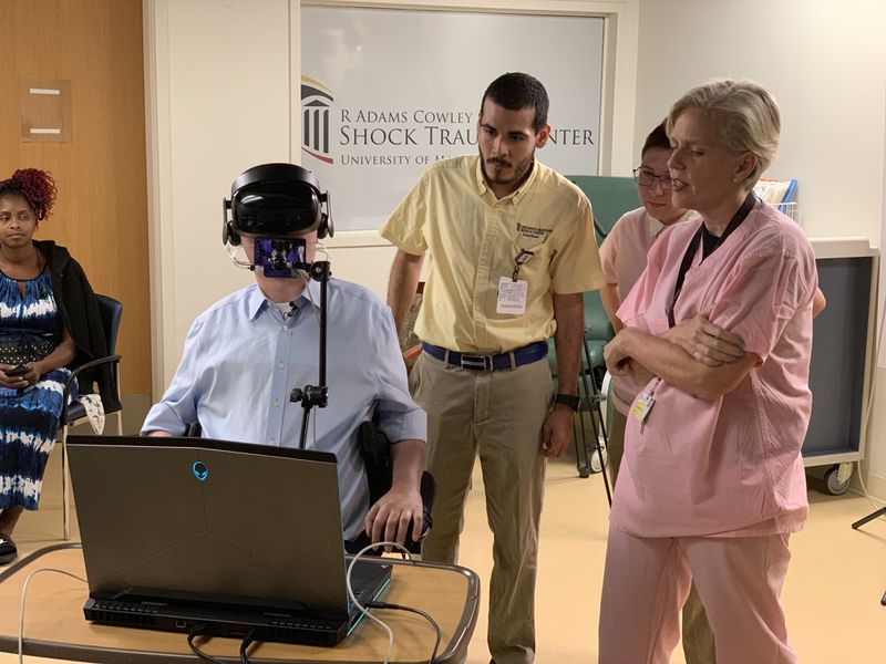 Joshua Basile (seated at computer) tests a virtual reality platform as MICA Game Lab interns Marco Cortes, left, and Nastia Garachtchenko, middle, watch alongside Dr. Sarah Murthi of Shock Trauma.