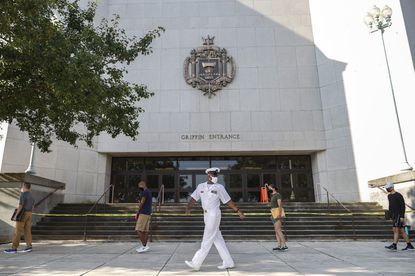 in this file photo, plebes socially distance themselves in line as a Naval officer (C) looks on, on Induction Day on June 30, 2020 at the U.S. Naval Academy in Annapolis, Maryland. The Naval Academy was named the nation's top public liberal arts college according to U.S. News & World Report's 2021 rankings.