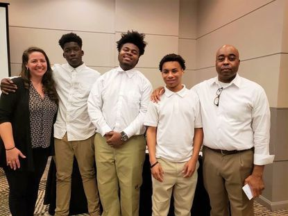 Esaiah Watson, center, leads one of the teams competing in Philanthropy Tank Baltimore. From left, Emily Mayock, adviser, students Dayvon Cummings, Watson, Devin Mintz, and Jonathan Moore, adviser.