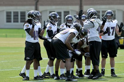 Defensive players huddle during the first day of the Ravens' rookie mini-camp. Newcomers and younger players will be key to the team's success this season.