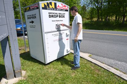 John Harris of Ellicott City drops off his primary election ballot at an official ballot drop box by the Meadowbrook Park Athletic Complex in Ellicott City on Saturday, May 23.
