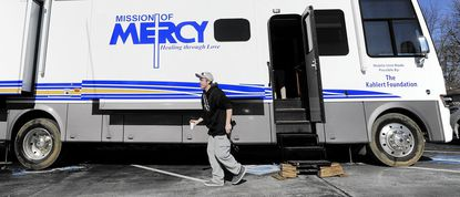 A client makes his way back to the church after seeing a Physician's Assistant in Mission of Mercy's new mobile unit outside Trinity Evangelical Lutheran Church in Taneytown in this February file photo.