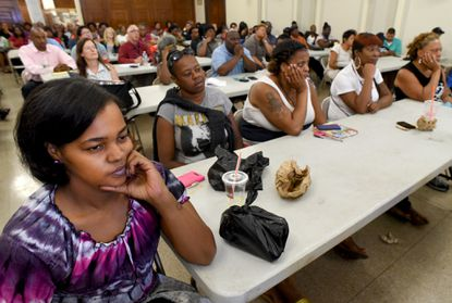 Tierra Smith, left, an employee at the Southeast Anchor branch of the Enoch Pratt Free Library listens with other city employees at an all-day trauma training program at the War Memorial building.
