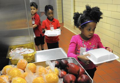 Natalia Carter stands in the lunch line at Beechfield Elementary School as the prekindergarten class gets their lunch. Starting this week, all students in the city will receive free lunch and breakfast.