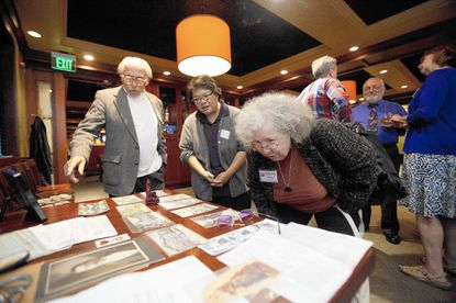 Albert Armstrong, left, of Ellicott City, Pat Villacrusis, of Charles Village, and Evelyn Herzog, right, of Federal Hill, look at a collection of props during a Watson's Tin Box meeting at Houlihan's in Columbia on Sept. 27. This year will mark the Howard County-based Sherlockian society's 25th anniversary.