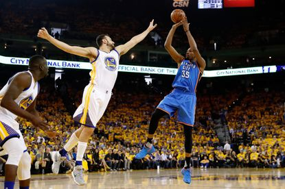 OAKLAND, CA -- Kevin Durant, #35, of the Oklahoma City Thunder takes a shot over Andrew Bogut, #12, of the Golden State Warriors during game one of the NBA Western Conference Final at ORACLE Arena on May 16, 2016 in Oakland, California.