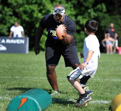 Tony Coaxum works with a youngster during a Ravens football clinic in Fallston.