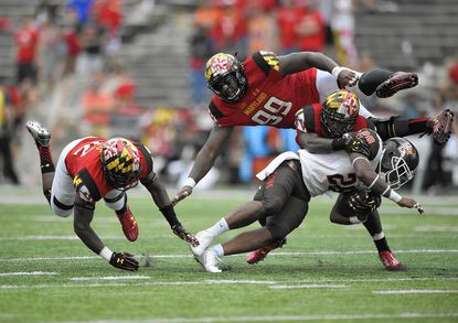 Bowling Green running back Fred Coppet (28) is tackled by Maryland defensive back Jarrett Ross, left, Quinton Jefferson, top right, and Anthony Nixon, second from right, during the second half of an NCAA college football game, Saturday, Sept. 12, 2015, in College Park, Md. Bowling Green won 48-27. (AP Photo/Nick Wass)