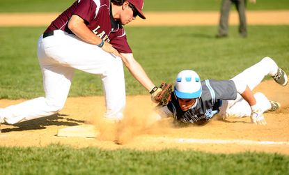 Pallotti 's Ryan Basile slides safely back to first base before Charles Lillie of Boys' Latin applies the tag in the Panthers' 7-3 win on April 26.