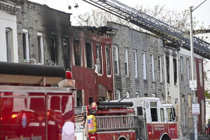 Fire crews work at the scene of a five-alarm fire in the 300 block S. Fulton Avenue in Southwest Baltimore.