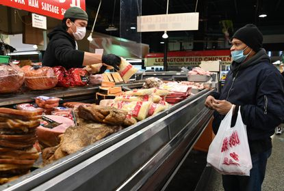 Jacob Kim an employee at the Buffalo Bill II, butcher stall at Lexington Market, helps Kevin Thomas of Baltimore with his purchase of sauerkraut and pig tails. November 23, 2020