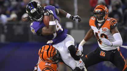 Ravens running back Alex Collins gains five yards on a third-quarter carry as he is brought down by Bengals linebacker Brandon Bell during the regular-season finale.