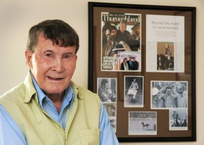 Joe Aitcheson, Hall of Fame steeplechase jockey, at the Carroll Lutheran Village in Westminster with a collage of framed photos and a magazine cover spanning his career.