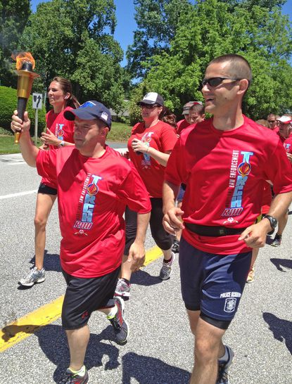 Michael Heup, left, of Davidsonville, carries Special Olympics torch on June 4 during the run from Glen Burnie to Annapolis, with Anne Arundel County Police Cpl. Mike Shier running beside him.