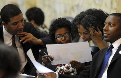 Baltimore delegates (from left) Keiffer Mitchell, Mary Washington, Jill Carter and Keith Haynes study a copy of a proposed redistricting map on the House of Delegates floor during debate Wednesday.