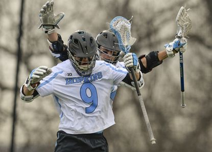 Johns Hopkins' Wilkins Dismuke (9) celebrates with teammate, Shack Stannic after putting the Blue Jays on top, 11-7 in the fourth quarter. Johns Hopkins tops Towson, 14-8 in a battle of ranked teams Saturday afternoon at Homewood Field in Baltimore.