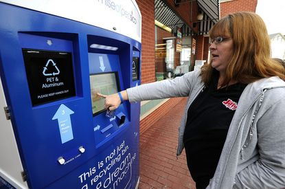 Mary Freyer, manager of Jiffy Mart on West Main Street in Westminster, demonstrates the new recycling machine located in front of the store.
