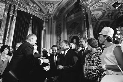 President Lyndon B. Johnson shakes the hand of Martin Luther King at an Aug. 6, 1965, event in Washington for the signing of the Voting Rights Act.