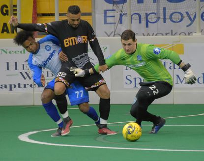 Utica City FC defender Stephen Deroux (77) tangles with Baltimore Blast forward Juan Pereira as goalkeeper Andrew Coughlin focuses on the free ball during Game One of the Eastern Division Finals last April.