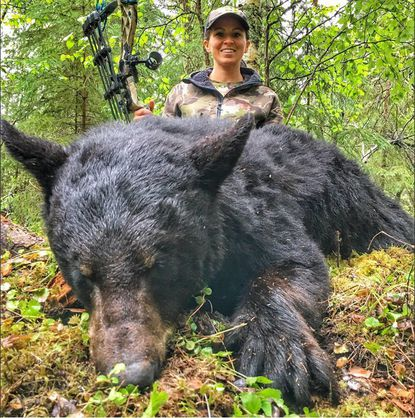 Under Armour tweeted this photo from its @UAHunt account of hunter Sarah Bowmar with a dead bear in June after she hunted it in Canada with a bow. The company terminated its contract with her last week after a video emerged that she shot of her husband spearing a bear to death.