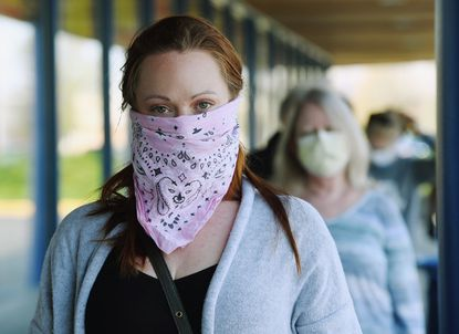 Kendall Klein wears a pink bandana to cover her face as she waits in line at Trader Joe's in Annapolis. Many in the Annapolis area are taking heed and wearing facial coverings and masks when out in public to help with COVID-19 Coronavirus mitigation.
